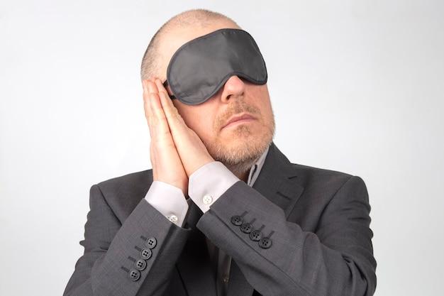 Homme D'affaires En Bandeau Pour Dormir Avec Les Bras Levés Pour Se Reposer Sur Un Fond Blanc Photo Premium
