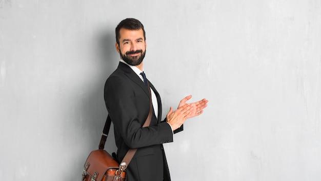 Homme d'affaires avec barbe applaudissant après présentation à une conférence Photo Premium