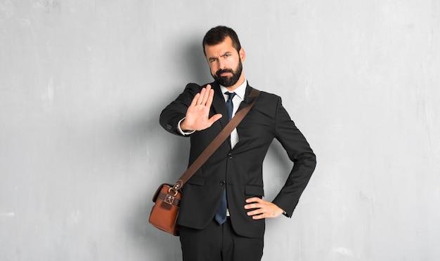 Homme d'affaires avec barbe faisant un geste d'arrêt niant une situation qui pense mal Photo Premium