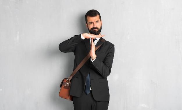 Homme d'affaires avec barbe faisant un geste d'arrêt avec sa main pour arrêter un acte Photo Premium