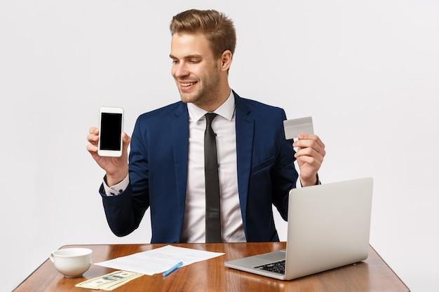 Homme D'affaires Barbu Blond Attrayant Au Bureau Avec Ordinateur Portable, Smartphone Et Carte De Crédit Photo Premium