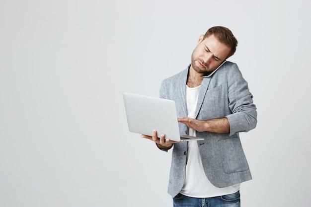 Homme D'affaires Beau Occupé Parlant Au Téléphone Et Utilisant Un Ordinateur Portable Photo gratuit
