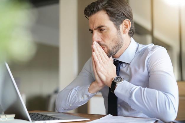 Homme d'affaires beau stressé regardant un ordinateur portable au bureau Photo Premium