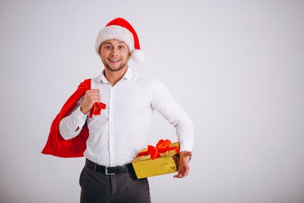 Homme d'affaires en bonnet de noel tenant le cadeau de noël isolé Photo gratuit