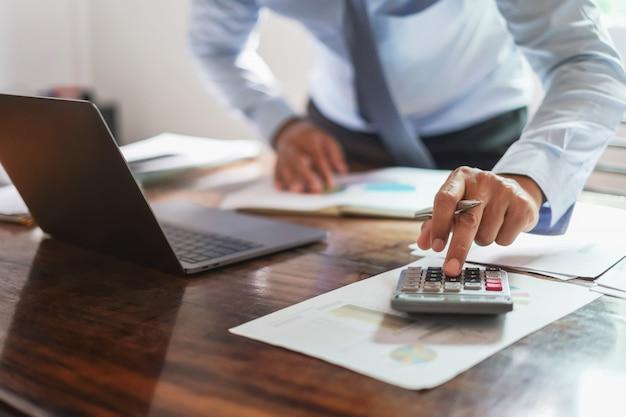 Homme affaires, bureau, bureau, utilisation, calculatrice, rapport argent Photo Premium