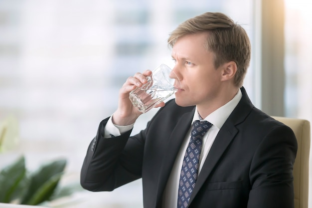 Homme d'affaires buvant de l'eau au bureau Photo gratuit