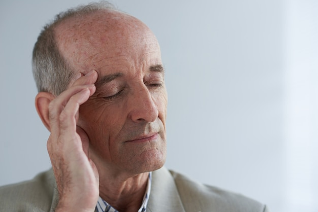 Homme d'affaires caucasien âgé masser le temple avec les yeux fermés Photo gratuit