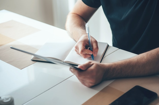 Homme D'affaires Caucasien, écrire Quelque Chose Dans Un Livre à L'aide D'une Tablette Pour Copier Photo Premium