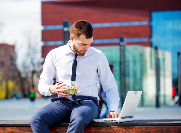 Homme d'affaires en chemise et cravate avec boîte à lunch salade Photo Premium
