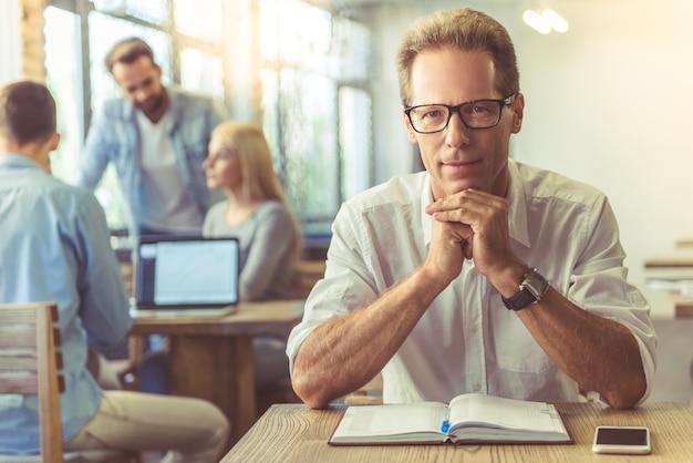 Homme d'affaires en chemise et lunettes regarde la caméra Photo Premium