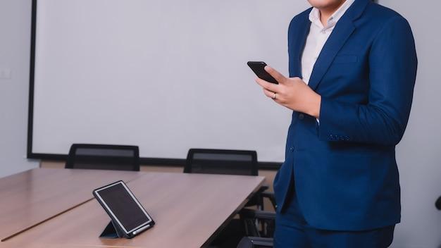 Homme d'affaires cherchant des données avec un smartphone entre la réunion de brainstorming Photo Premium