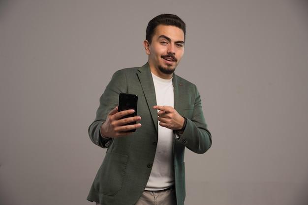 Un Homme D'affaires En Code Vestimentaire Faisant La Promotion D'un Smartphone. Photo gratuit