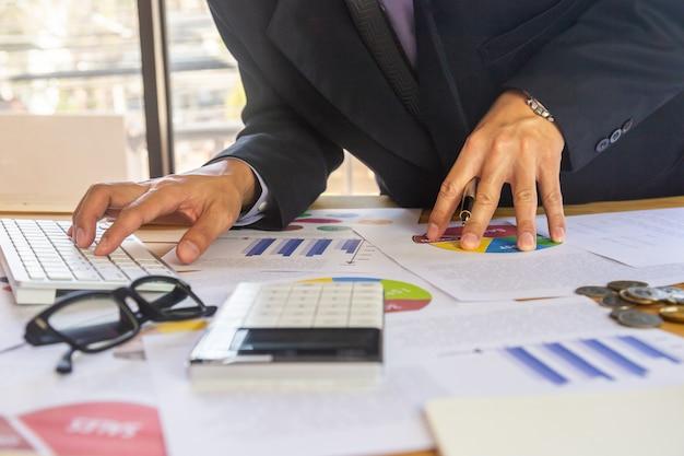 Homme d'affaires ou un comptable travaillant sur la calculatrice pour calculer le concept de données d'entreprise. Photo Premium
