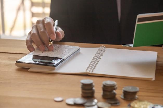 Homme d'affaires ou un comptable travaillant sur la calculatrice pour calculer le concept d'entreprise. Photo Premium