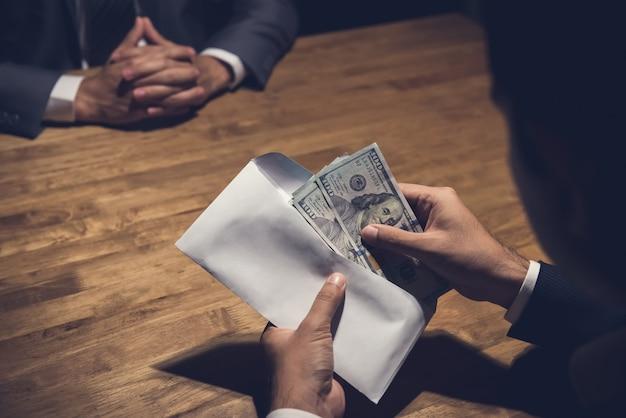 Homme d'affaires comptant de l'argent dans l'enveloppe que vient de donner son partenaire Photo Premium