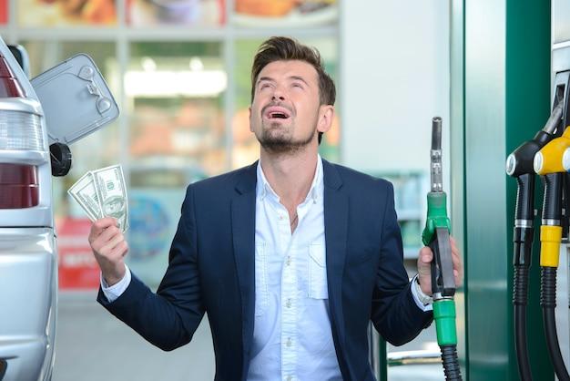 Homme affaires, compter argent, essence, ravitaillement Photo Premium
