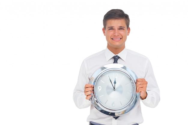 Homme d'affaires concerné tenant l'horloge Photo Premium