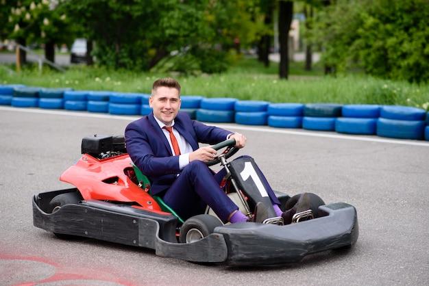 Homme d'affaires conduisant un véhicule d'enfant. Photo Premium