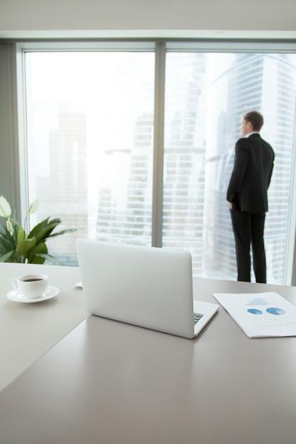 Homme d'affaires confiant contemplant dans son bureau Photo gratuit