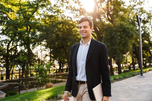 Homme D'affaires Confiant, Marchant à L'extérieur, Portant Un Ordinateur Portable Photo Premium