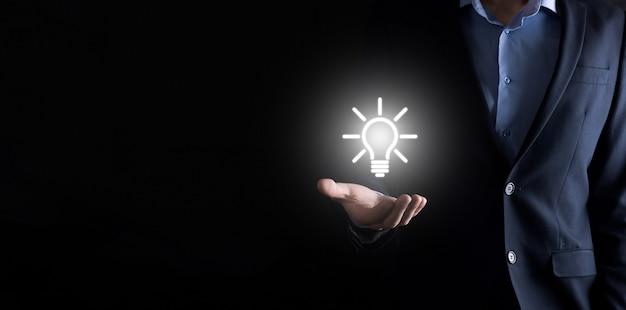 Homme D'affaires En Costume Avec Une Ampoule Dans Ses Mains. Tient Une Icône Idée Rougeoyante Dans Sa Main. Avec Une Place Pour Le Texte. Photo Premium