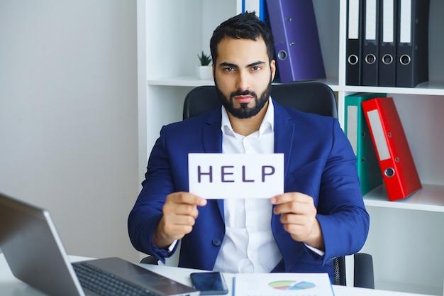 Homme d'affaires en costume-cravate assis au bureau travaillant sur un ordinateur portable demandant de l'aide tenant une pancarte en carton Photo Premium
