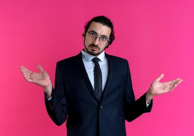 Homme D'affaires En Costume Noir Et Lunettes à L'avant Avec Les Mains Levées Avec Expression Confuse Debout Sur Le Mur Rose Photo gratuit