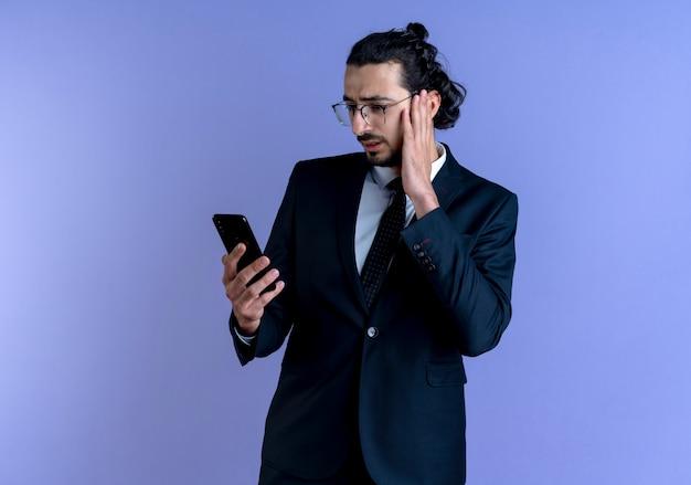 Homme D'affaires En Costume Noir Et Lunettes Regardant L'écran De Son Smartphone Avec Une Expression De Confusion Debout Sur Un Mur Bleu Photo gratuit