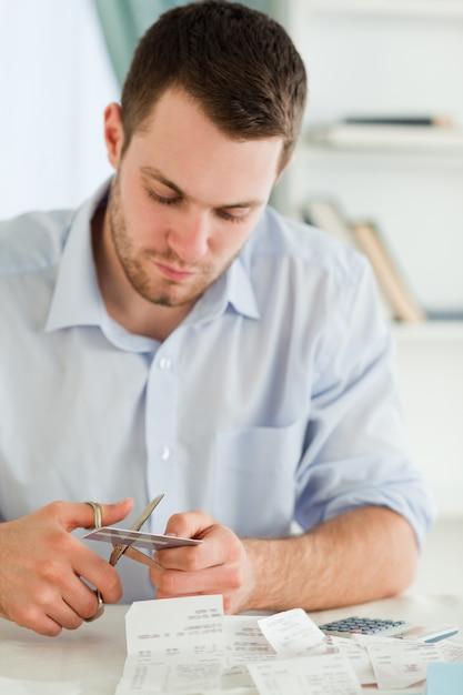 Homme d'affaires coupant sa carte de crédit en morceaux Photo Premium