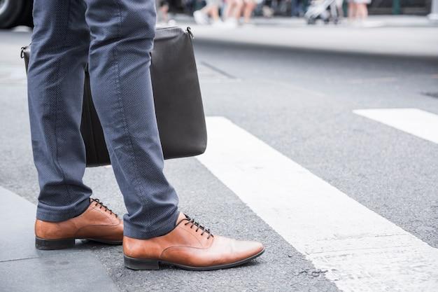 Homme d'affaires de culture debout près du passage pour piétons Photo gratuit