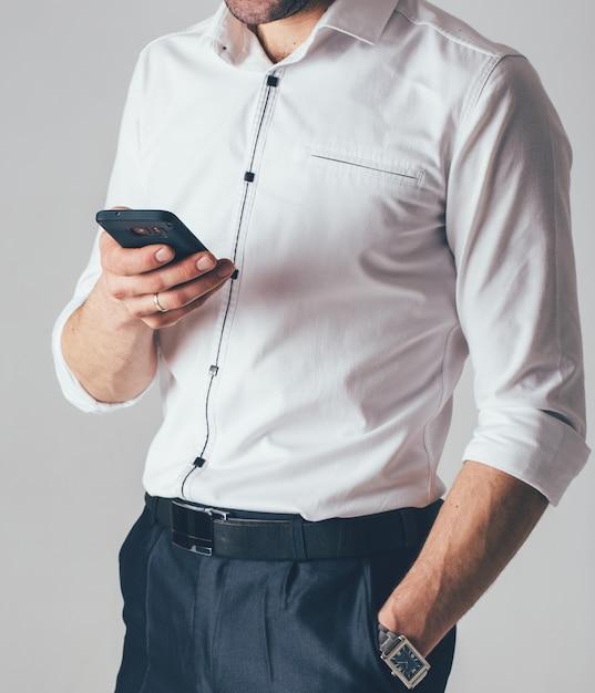 Un homme d'affaires dans une chemise blanche et un pantalon noir tient un téléphone à la main dans le bureau. un homme porte une montre au poignet dans sa main gauche Photo Premium