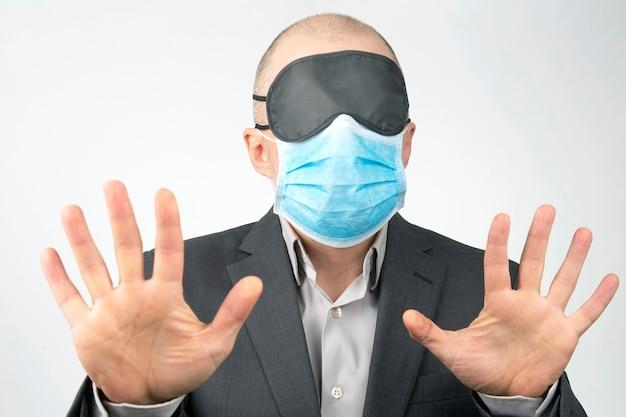 Homme D'affaires Dans Un Masque Médical Et Les Yeux Bandés Pour Dormir Avec Les Mains Sur Un Blanc Photo Premium
