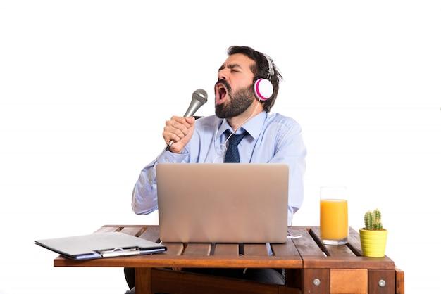 Homme d'affaires dans son bureau chantant Photo gratuit