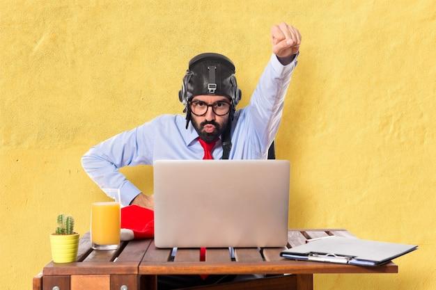 Homme d'affaires dans son bureau avec chapeau pilote Photo gratuit