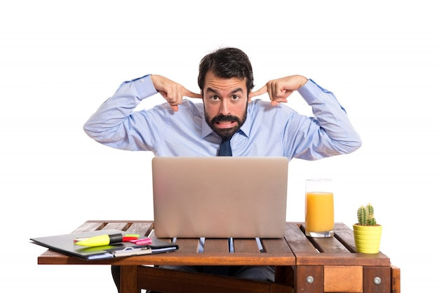 Homme d'affaires dans son bureau couvrant ses oreilles Photo gratuit