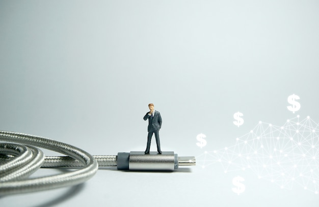 Homme d'affaires debout sur un câble usb de type c usb. concept de commerce électronique Photo Premium