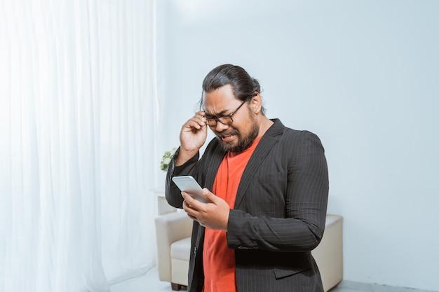 Homme D'affaires Déçu De Recevoir Un Message Texte Sur Son Smartphone Photo Premium