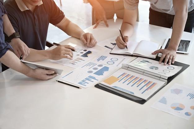 Homme d'affaires de démarrage rencontre avec papier finance travaille sur le bureau. Photo Premium