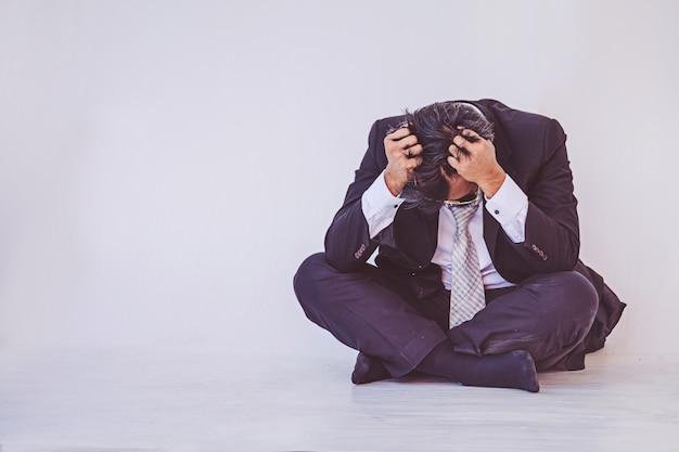 Homme d'affaires déprimé assis sur le sol Photo Premium