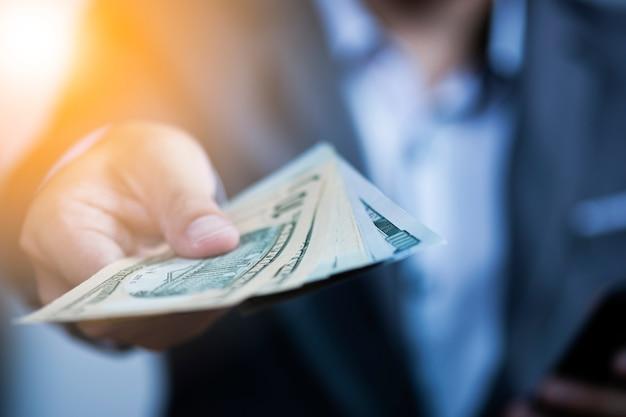 Homme d'affaires détenant des billets en dollars américains pour le paiement. Photo Premium