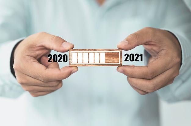 Homme D'affaires Détenant Un Bloc De Cube En Bois Qui Imprime Le Chargement De L'écran Pour L'année 2020 à L'année 2021, Démarrer Un Nouveau Concept D'entreprise. Photo Premium
