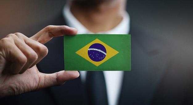 Homme d'affaires détenant la carte du drapeau du brésil Photo Premium