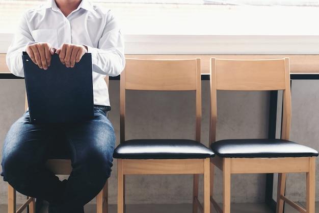 Homme d'affaires détenant un rapport de portefeuille assis sur une chaise Photo Premium