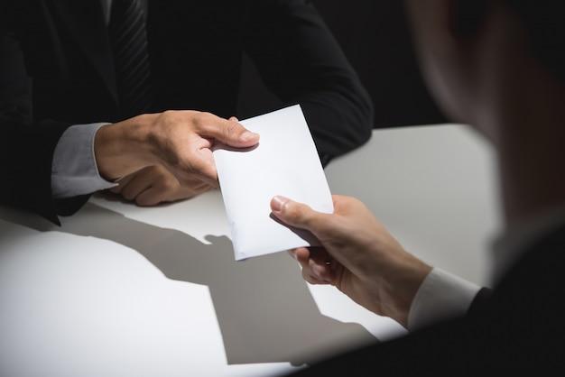 Homme d'affaires donnant de l'argent dans l'enveloppe pour partenaire Photo Premium