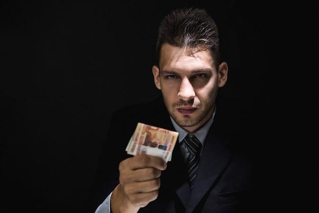 Homme d'affaires donnant de l'argent sous forme de rouble russe dans une pièce sombre Photo Premium