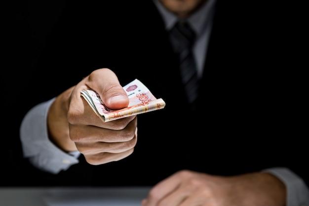 Homme d'affaires donnant secrètement de l'argent dans le noir Photo Premium