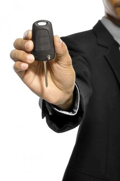 Homme d'affaires donne une clé de voiture isolée sur fond blanc Photo Premium