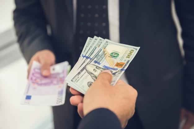 Homme D'affaires échangeant De L'argent Avec Des Dollars Américains En Euros Photo Premium