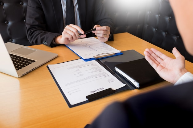 Homme d'affaires écouter un jeune homme attrayant expliquer ses réponses à l'entretien d'embauche de profil Photo Premium