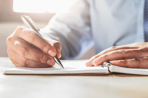Homme d'affaires écrit sur le carnet de notes au bureau Photo Premium